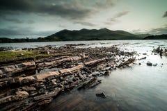 Stenig kust på Killarney sjön Arkivbild