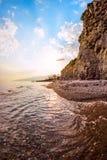 Stenig kust på solnedgången Arkivfoto