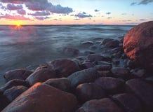 stenig kust Stenar i havsvågorna beautiful clouds Solnedgång nn Royaltyfri Fotografi