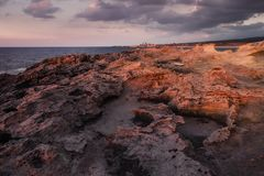 Stenig kustlinje i ljuset av solnedgången Royaltyfri Fotografi