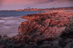 Stenig kustlinje i ljuset av solnedgången Royaltyfri Foto