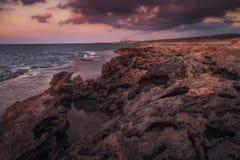 Stenig kustlinje i ljuset av solnedgången Arkivfoto