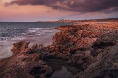 Stenig kustlinje i ljuset av solnedgången Fotografering för Bildbyråer