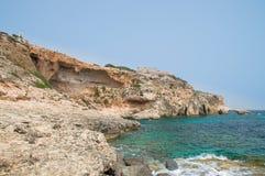 Stenig kustlinje med batteriet för St Mary ` s i den Comino ön i Malta Fotografering för Bildbyråer