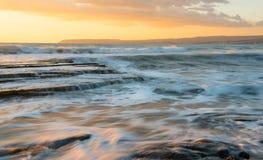 Stenig kustseascape med det krabba havet under solnedgång fotografering för bildbyråer