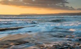 Stenig kustseascape med det krabba havet under solnedgång royaltyfri foto