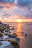 Stenig kustsolnedgång Arkivbild