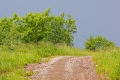 Stenig och smutsig lantlig väg bland ängar och buskar under mörker s Royaltyfri Foto