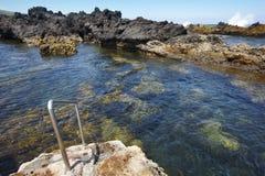 Stenig pölstrand med trappa i Biscoitos Terceira ö Azor Arkivfoto