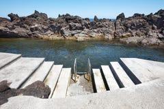 Stenig pölstrand med trappa i Biscoitos Terceira ö Azor Fotografering för Bildbyråer