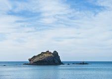 Stenig purpurfärgad ö i havet Royaltyfri Fotografi
