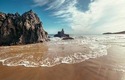 Stenig sandstrand på havstranden Arkivfoto