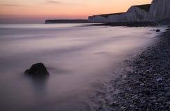 Stenig shoreline för långt exponeringslandskap på solnedgången Arkivfoton