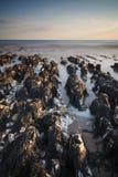 Stenig shoreline för långt exponeringslandskap på solnedgången Fotografering för Bildbyråer