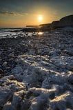Stenig shoreline för långt exponeringslandskap på solnedgången Royaltyfria Bilder