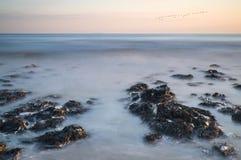 Stenig shoreline för långt exponeringslandskap på solnedgången Arkivfoto
