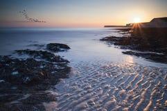 Stenig shoreline för långt exponeringslandskap på solnedgången Arkivbilder