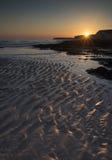 Stenig shoreline för långt exponeringslandskap på solnedgången Royaltyfri Bild