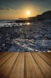 Stenig shoreline för långt exponeringslandskap på solnedgången med träpl Arkivbild