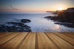 Stenig shoreline för långt exponeringslandskap på solnedgången med träpl Arkivfoton