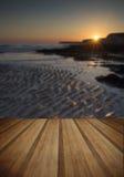Stenig shoreline för långt exponeringslandskap på solnedgången med träpl Arkivbilder