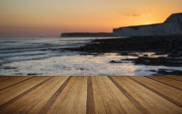 Stenig shoreline för långt exponeringslandskap på solnedgången med träpl Royaltyfri Fotografi