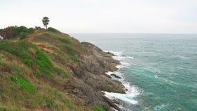 Stenig shoreline längs det öppna havet Vågorna bryter på en klippa som täckas med gröna växter lager videofilmer