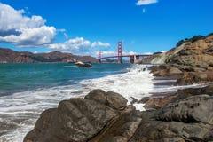 Stenig shoreline och Golden gate bridge i San Francisco. royaltyfria foton
