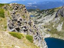 Stenig sikt till delar av två av de sju Rila sjöarna i Rila berg, Bulgarien - den tvilling- och fisk sjön Arkivfoto