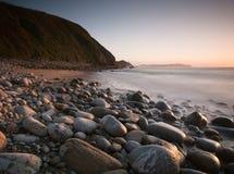 stenig solnedgång för strand Arkivfoto