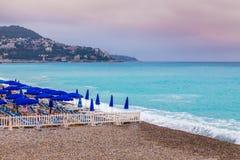 Stenig stadsstrand med Deckchairs-Nice, Frankrike Arkivbild