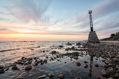 Stenig strand för gammal fyr på solnedgångtimmen Arkivfoto