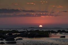 Stenig strand för solnedgång, fridsamt hav, orange himmel Royaltyfri Fotografi