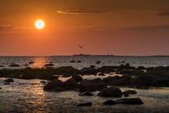 Stenig strand för solnedgång, fridsamt hav, orange himmel Arkivfoton