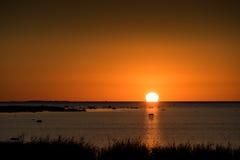 Stenig strand för solnedgång, fridsamt hav, orange himmel Kihnu liten ö i Estland Royaltyfri Bild