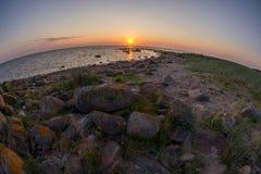 Stenig strand för solnedgång, fridsamt hav, orange himmel Kihnu liten ö i Estland Baltiskt hav, Europa Bakgrund för naturlig milj Royaltyfria Bilder
