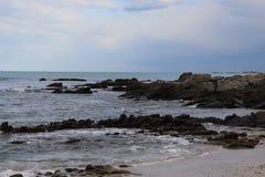 Stenig strand med lynniga himlar arkivbild