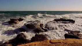 Stenig strand med turbulent vatten och avbrott av havvågor stock video