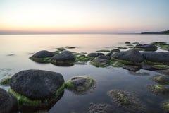 Stenig strand på solnedgången med mjölkaktigt vatten arkivbilder