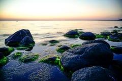 Stenig strand på solnedgången med mjölkaktigt vatten royaltyfria foton