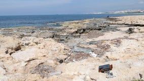 Stenig strand som f?rorenas med plast- flaskor och avfall Fiskare och skepp på bakgrunden arkivfilmer