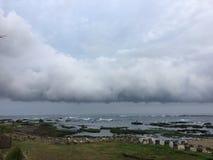 Stenig strandremsa och lågt moln över havet Arkivfoto