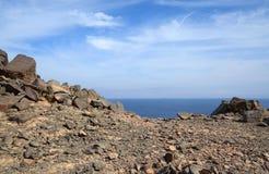 Stenig terräng på en bakgrund av havet och himmel Arkivfoton