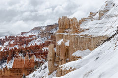 Stenig utlöpare med snö, Bryce Canyon, hoodos i bakgrunden Arkivbild