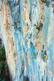 Stenig vägg för hög ovanlig färg och två klättrare som stiger royaltyfri foto
