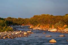 Steniga flodbanker med låg-tänt av solen Royaltyfri Fotografi