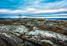 Steniga granitoutcroppings under en härlig blå molnig himmel på skymning, hög poängmonument upptill av NJ i vinter royaltyfri foto