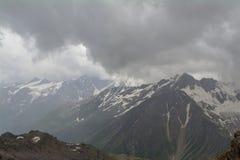 Steniga maxima med insnöat molnen, norr Kaukasus Elbrus region Royaltyfri Bild