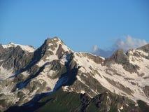 Steniga maxima och stenar med insnöade Caucasian berg i Georgia Fotografering för Bildbyråer