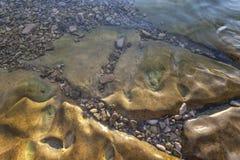 Steniga plattor på kust Arkivbild